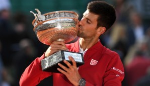 PARIS, FRANCE - JUNE 05:  Champion Novak Djokovic of Serbia kisses the trophy following his victory during the Men's Singles final match against Andy Murray of Great Britain on day fifteen of the 2016 French Open at Roland Garros on June 5, 2016 in P...